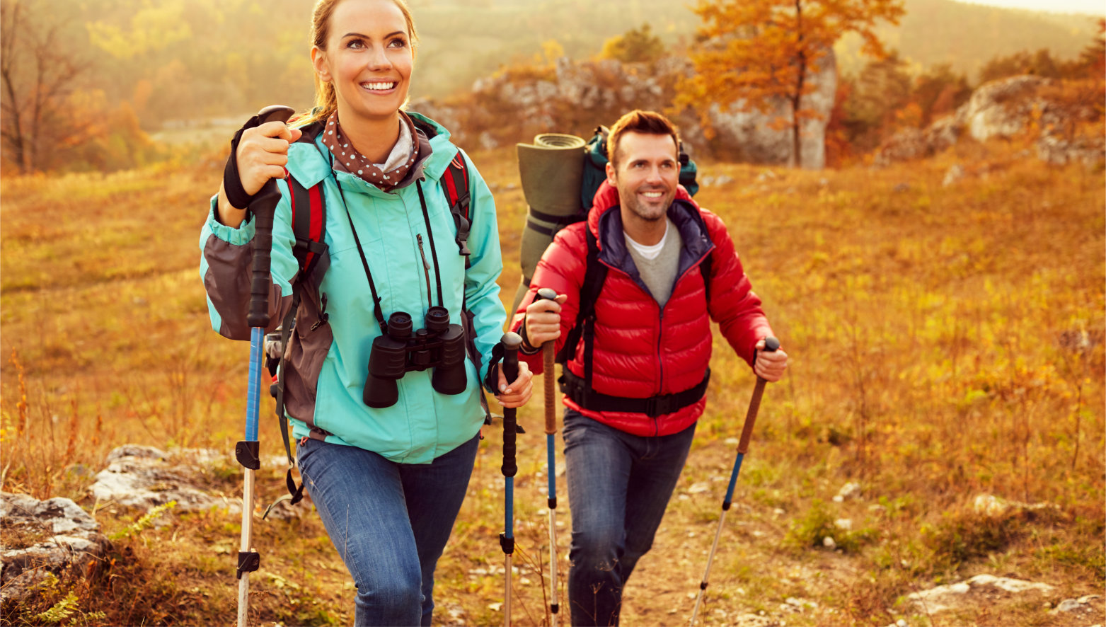 Couple,Hiking,During,Autumn,Vacation,With,Sticks,And,Backpacks